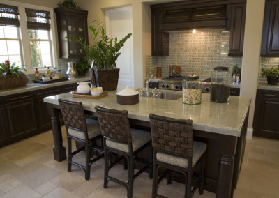 Modern designer kitchen with brown tiles and a granite island.